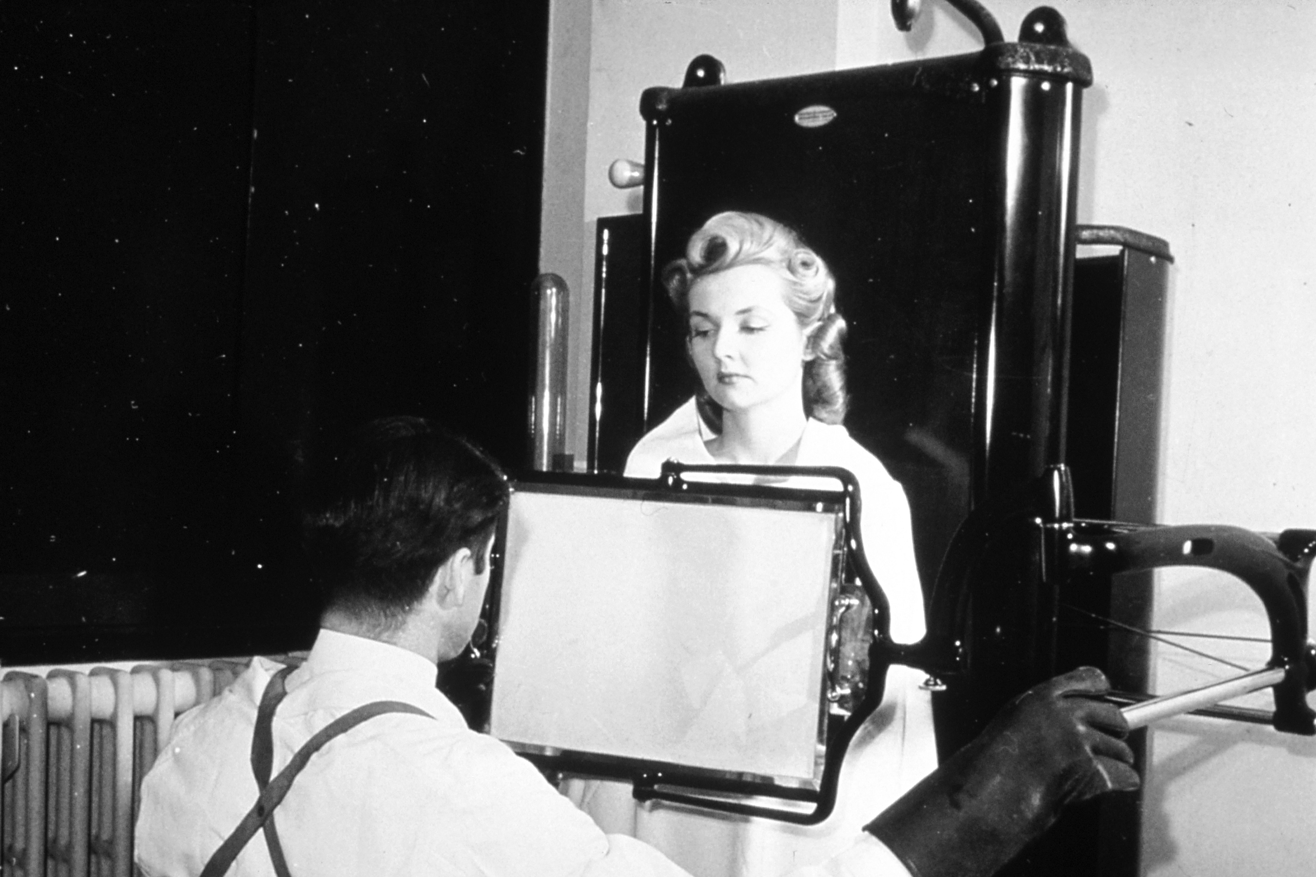 A male technician taking an X-ray of a female patient in 1940